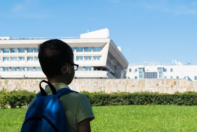 De student met een rugzak op zijn rug bekijkt het schoolgebouw stock fotografie