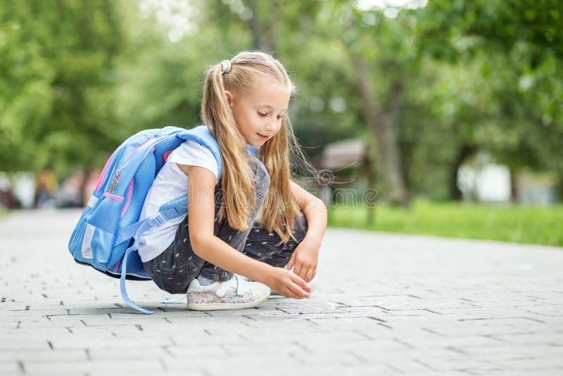 De student trekt krijt op het asfalt in het schoolplein Het concept school, studie, onderwijs, vriendschap, kinderjaren stock fotografie