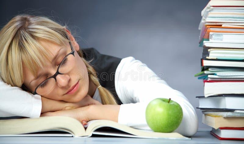 De student van de vermoeidheid in bibliotheek stock afbeelding