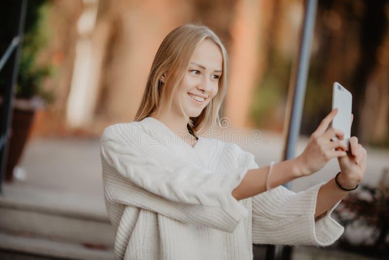 De student van het close-up selfie-portret van aantrekkelijk meisje in zonnebril met lang kapsel en sneeuwwitte glimlach in stad stock afbeelding