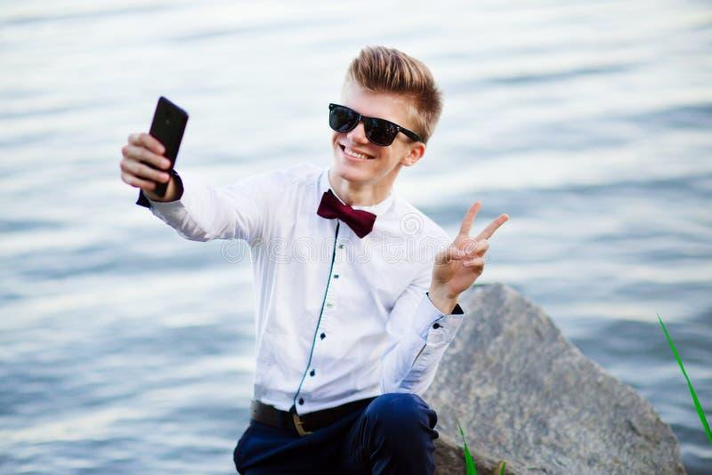 De student van de de mensenzakenman van het Selfieportret het ontspannen op strandoverzees die v-teken tonen knap en jong manneli stock foto's