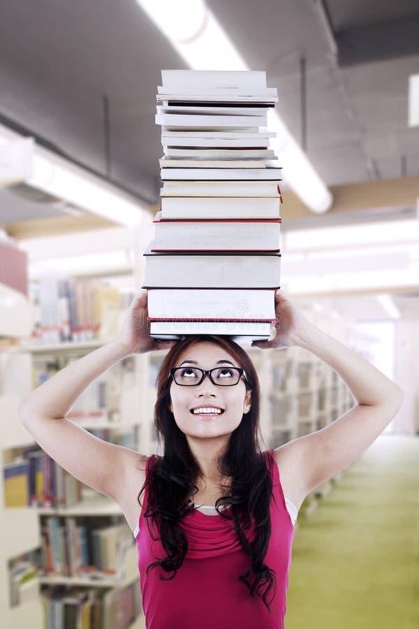 De studente draagt boeken op hoofd stock afbeelding