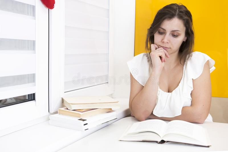 De studente leest boek en treft voor examens voorbereidingen bij universiteit royalty-vrije stock afbeeldingen