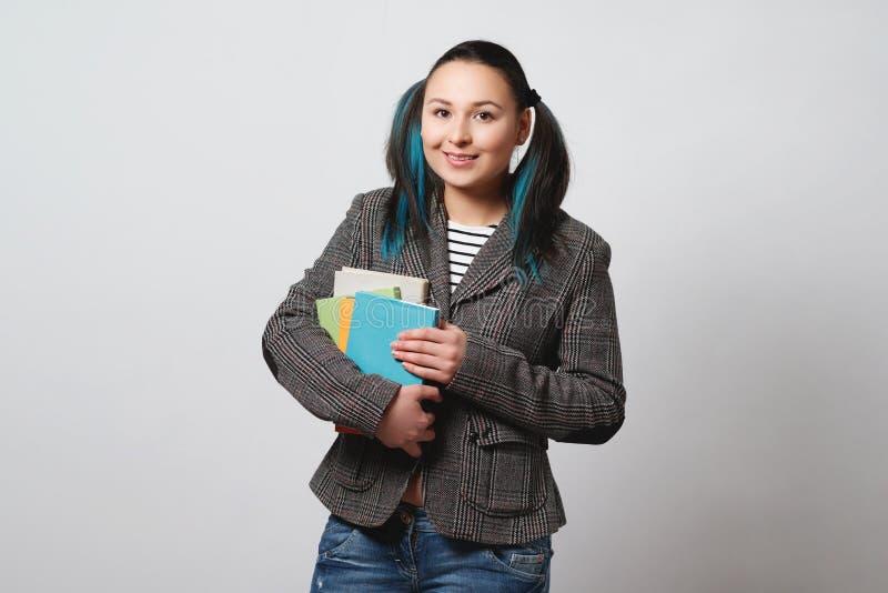 De studente met een stapel boeken in haar handen bekijkt de camera en glimlacht op lichte achtergrond stock fotografie