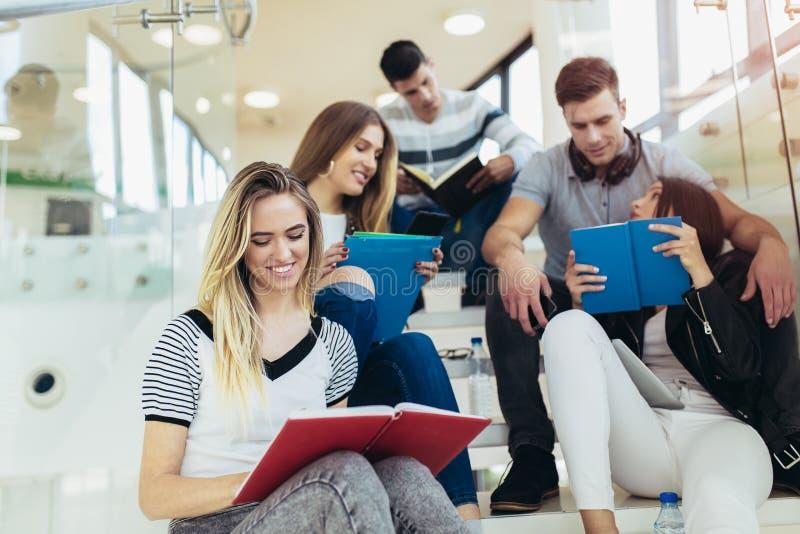De studenten bestuderen in bibliotheek De jongeren brengt samen tijd door Lezingsboek en het communiceren terwijl stock afbeelding