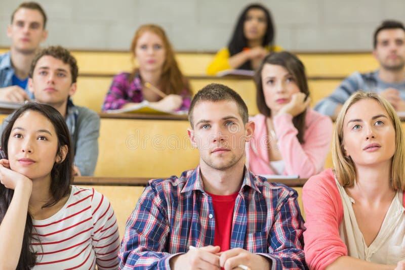 De studenten bij de universiteit spreken zaal royalty-vrije stock afbeeldingen