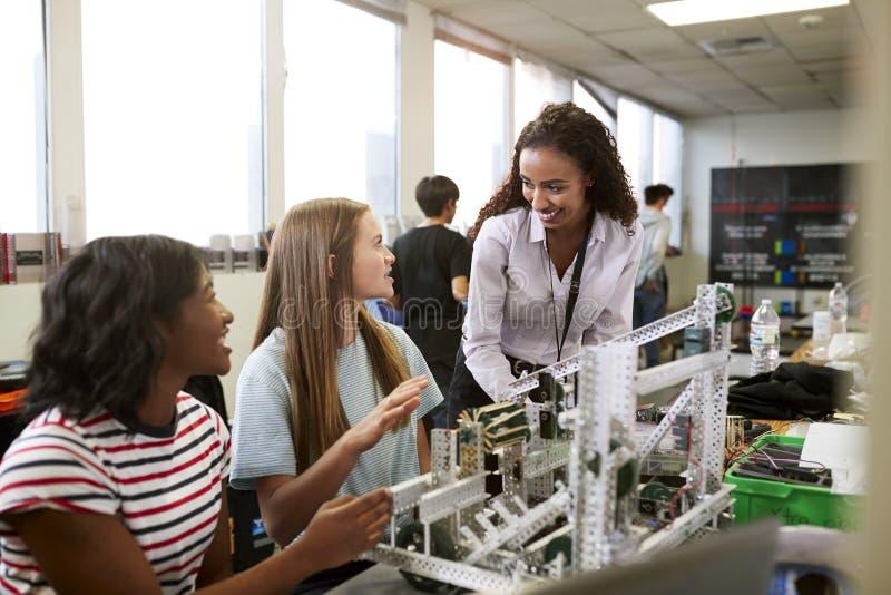 De Studenten die van With Female College van de vrouwenleraar Machine in van de Wetenschapsrobotica of Techniek Klasse bouwen stock afbeelding