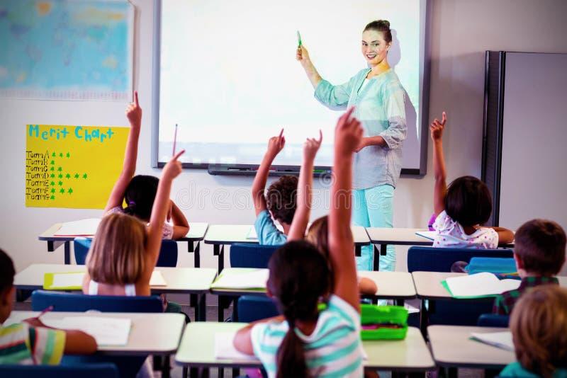 De studenten die van het leraarsonderwijs projector in klaslokaal met behulp van stock fotografie