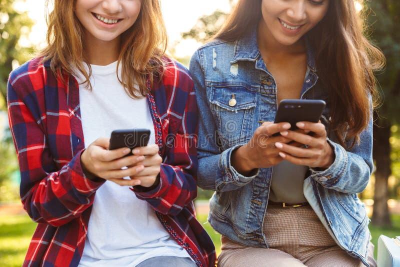 De studenten die van vrouwenvrienden in het park lopen die mobiele telefoon met behulp van royalty-vrije stock afbeeldingen