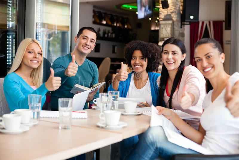 De studenten in koffie het tonen beduimelt omhoog royalty-vrije stock foto's