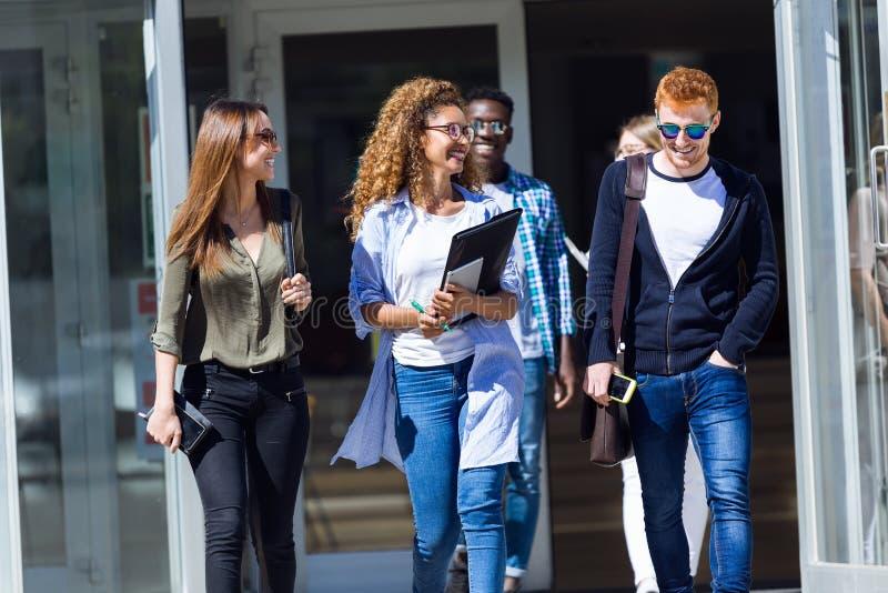 De studenten lopen in universitaire zaal tijdens onderbreking en het communiceren stock afbeeldingen