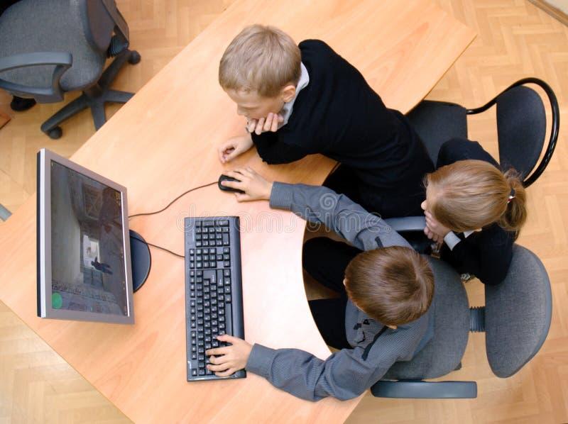 De studenten spelen een computerspel stock foto's