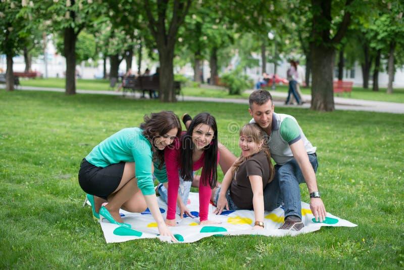 De studenten spelen een spel in het park twister stock foto's