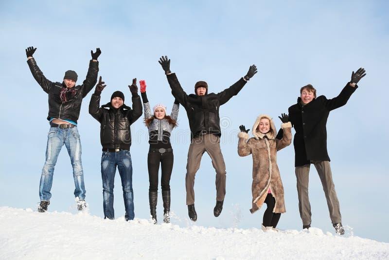 De studenten springen in de winter op sneeuw stock afbeeldingen