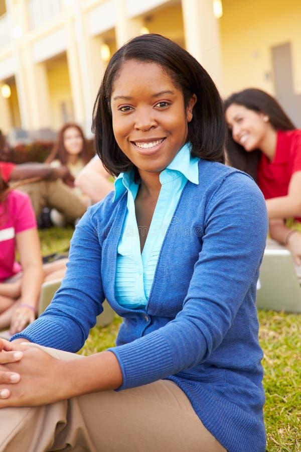 De Studenten van Sitting Outdoors With van de middelbare schoolleraar op Campus stock afbeeldingen