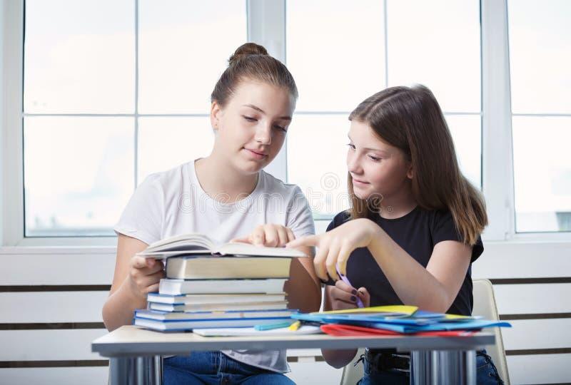 De studenten van tienerstienerjaren zitten bij de lijst met boeken st royalty-vrije stock afbeeldingen