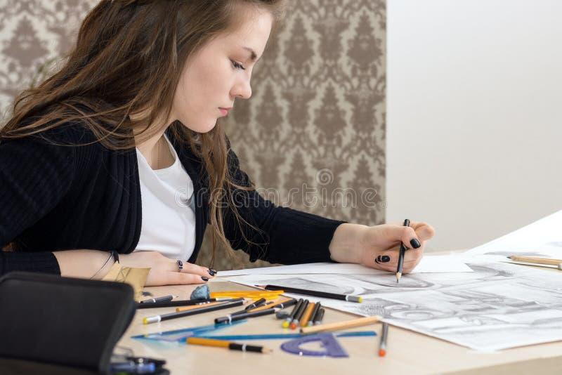 De studentenarchitect trekt een plan, grafiek, ontwerp, geometrische vormen door potlood op groot blad van document bij bureau stock afbeeldingen