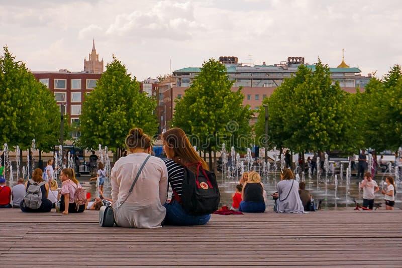 De studentenmeisjes die op de bank zitten, die in het park rusten, springen in Moskou op stock afbeelding