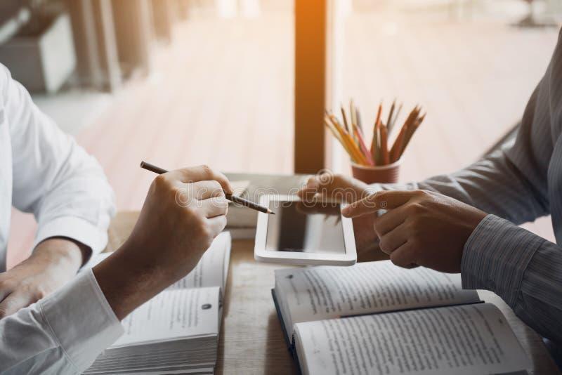 De studentenvrienden gebruiken tabletten die naar informatie over het uitbrengen van verslag op zoek zijn die leraren in klasse s royalty-vrije stock afbeeldingen