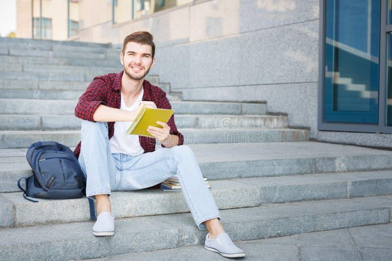 De studentenzitting van Nice op de de treden en het schrijven nota's in openlucht royalty-vrije stock foto's