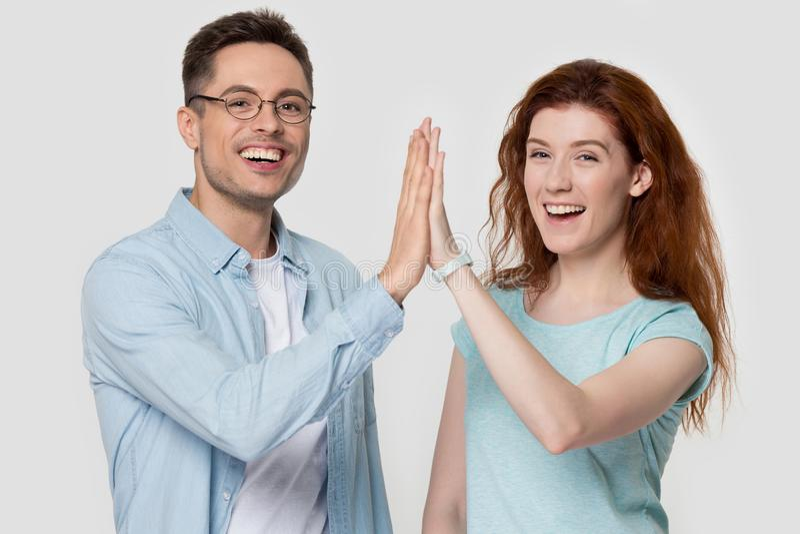 De studio schoot gelukkig millennial paar die hoog vijf handengebaar geven stock foto