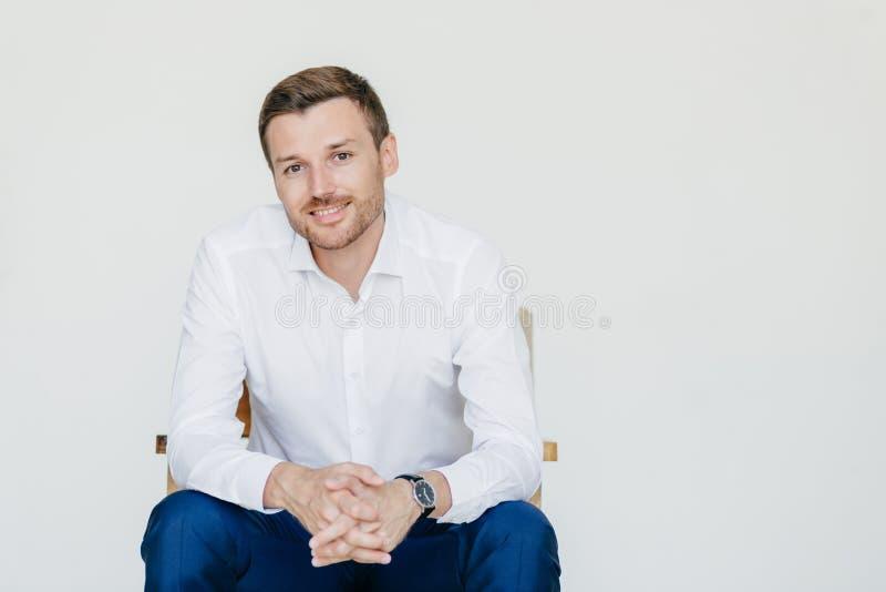 De studio van elegante vrolijke mannelijke die ondernemer in formele kleding wordt, zit op stoel, stelt bij camera, over witte ba royalty-vrije stock afbeeldingen