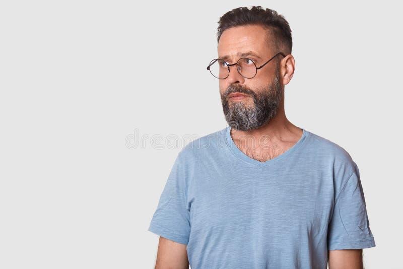 De studio van jong gebaard aantrekkelijk mannetje met baard wordt geschoten, die toevallig t shit en bril dragen die, ziet merkwa royalty-vrije stock afbeelding