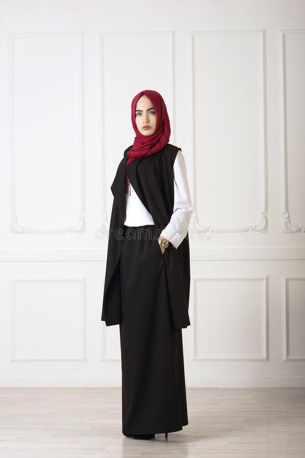 De studiofoto van een oosterse vrouw in een moderne Moslimkleding, een sjaal en een goud letten goed op hand royalty-vrije stock fotografie
