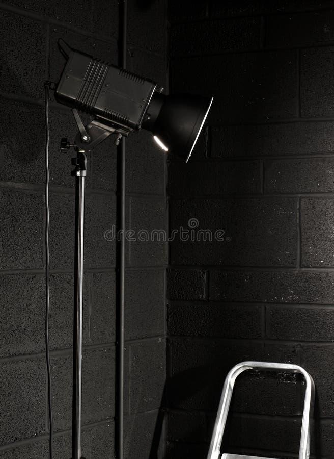 De studiolicht van de fotografie tegen een zwarte baksteen wal stock foto