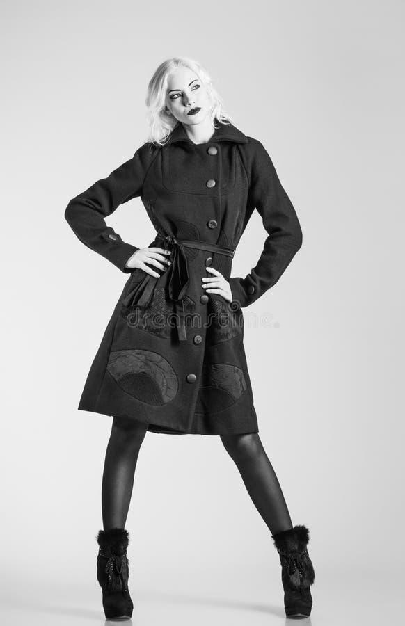 De studiomanier schoot: mooi meisje in zwarte laag en laarzen. Zwart-wit royalty-vrije stock foto