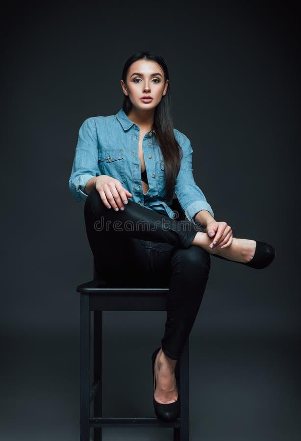 De studiomanier schoot: mooie jonge vrouw in jeans en overhemdszitting op bank royalty-vrije stock afbeelding
