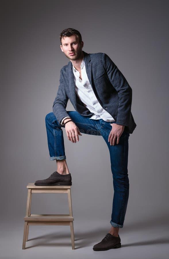 De studiomanier schoot: portret van de knappe jonge mens die jeans, overhemd en jasje draagt stock foto's