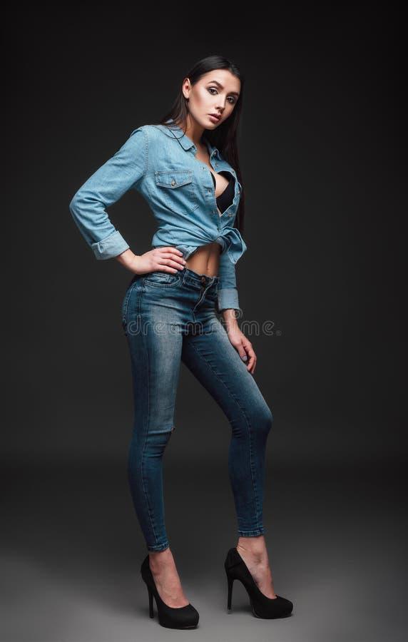 De studiomanier schoot: portret van mooie jonge vrouw in jeans en overhemd stock fotografie