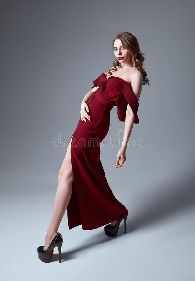 De studiomanier schoot: portret van sensuele mooie jonge vrouw in rode kleding stock fotografie
