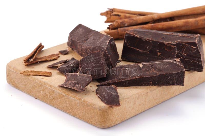 De stukken en de kaneel van de chocolade op een houten raad stock foto's