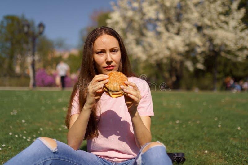 De succesvolle bedrijfsvrouw die snel voedselhamburger eet cheesburger geniet van haar vrije tijdsvrije tijd in een park met het  royalty-vrije stock afbeelding