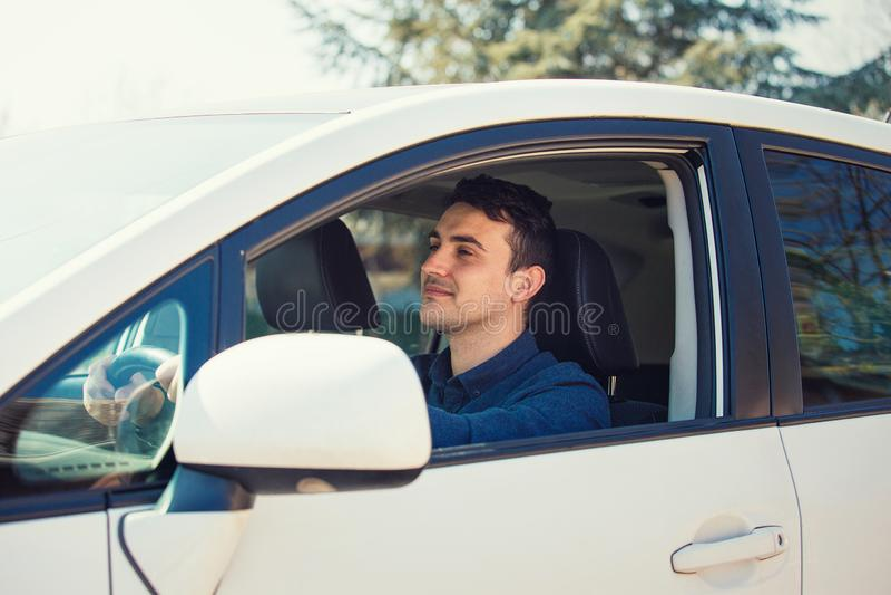 De succesvolle jonge mens die zijn nieuwe witte auto drijven houdt hand op de stuurwiel het vooruitzien gelukkige gevoelsbrandkas royalty-vrije stock afbeeldingen