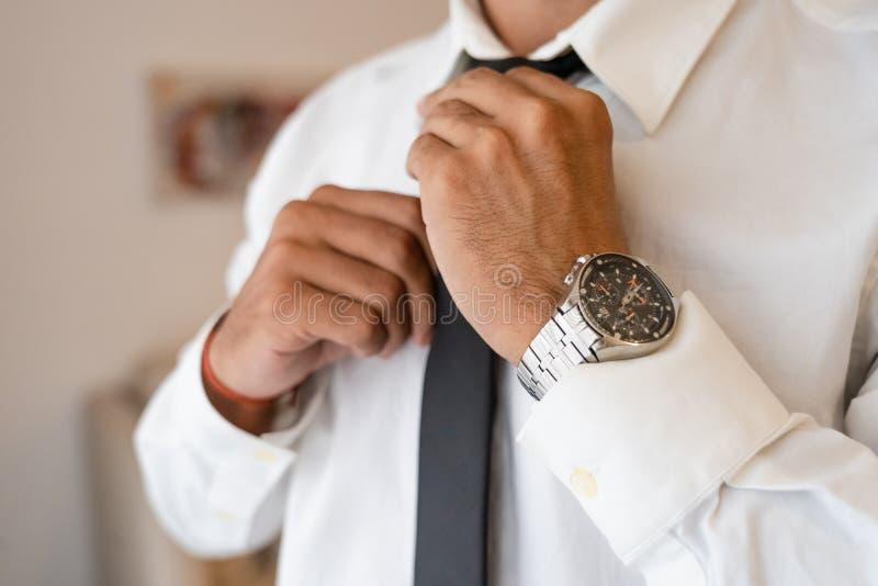 De succesvolle mens met wit overhemd bindt stropdas stock afbeeldingen