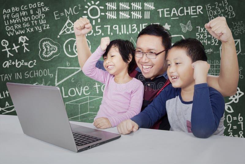 De succesvolle studenten met hun leraar heffen handen op stock fotografie