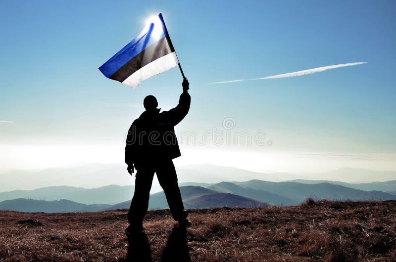 De succesvolle winnaar die van de silhouetmens Estlandse vlag bovenop de berg golven stock afbeelding