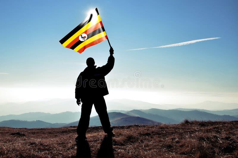 De succesvolle winnaar die van de silhouetmens de vlag van Oeganda golven royalty-vrije stock fotografie
