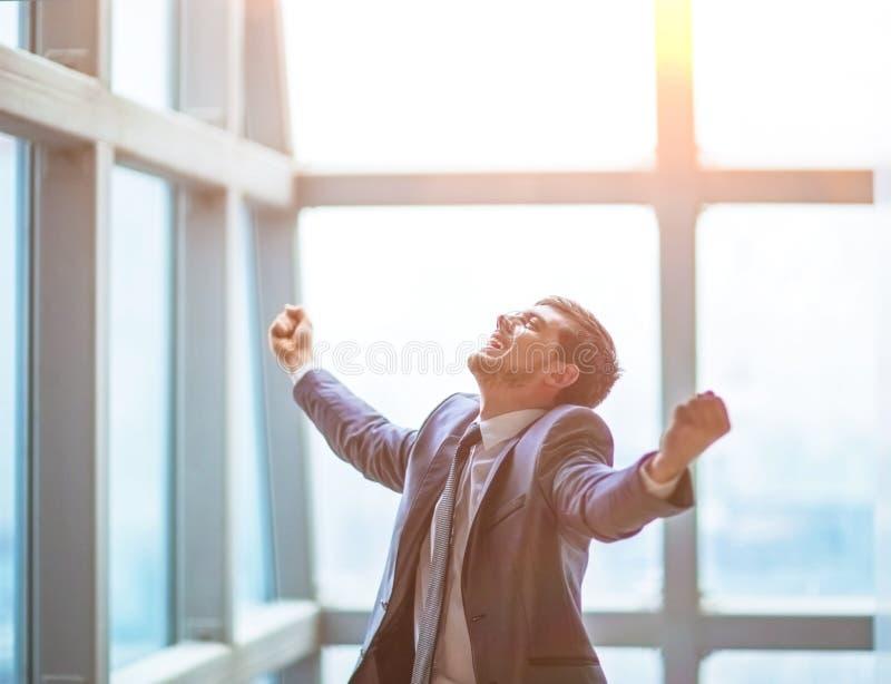 De succesvolle zakenman heft zijn handen op viert omhoog overwinning stock fotografie