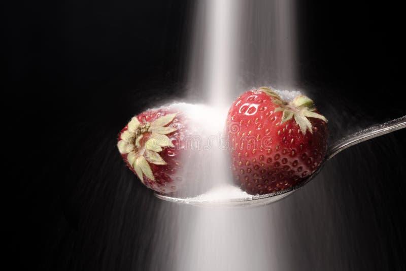 De suiker giet op de lepel met aardbei stock foto