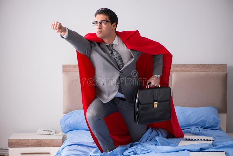 De super heldenonderneemster die in bed werken stock foto