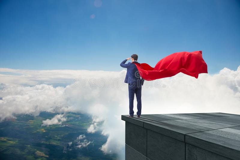 De super heldenzakenman bovenop de bouw klaar voor uitdaging royalty-vrije stock foto