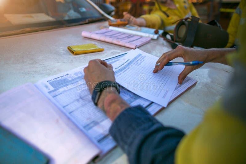 De supervisor die van de bouwmijnwerker veiligheid leiden die bij de analyse van baangevaren van hete het werkvergunning vóór tek royalty-vrije stock foto's