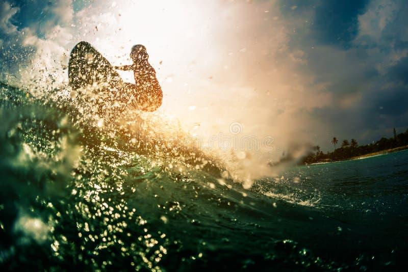 De surfer berijdt de golf stock fotografie
