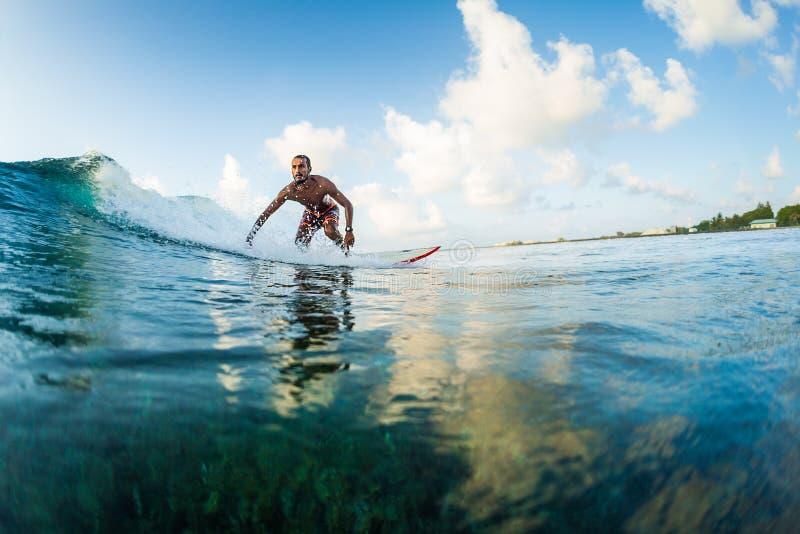 De surfer berijdt de golf stock afbeelding