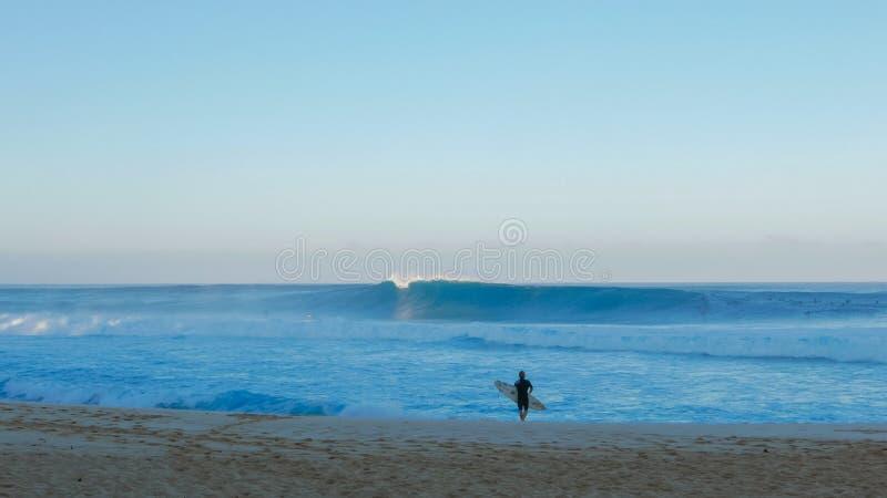 De surfer let op pijpleiding en wacht alvorens uit te paddelen stock afbeelding
