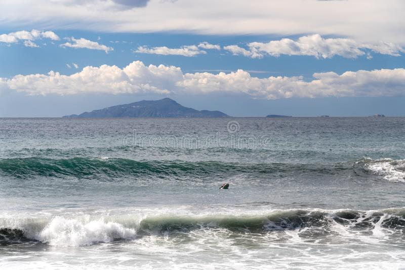 De surfer neemt een golf, op een surfplank, glijdt langs de golf, op de achtergrond van de berg, Sorrento Itali? royalty-vrije stock foto